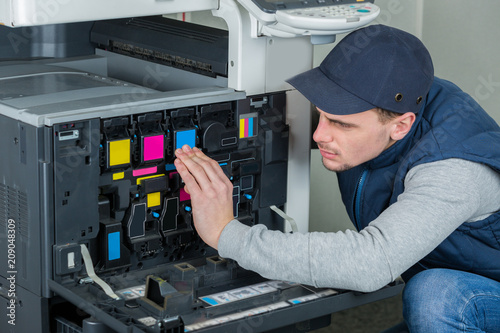 Cuadros en Lienzo young male technician repairing digital photocopier printer machine