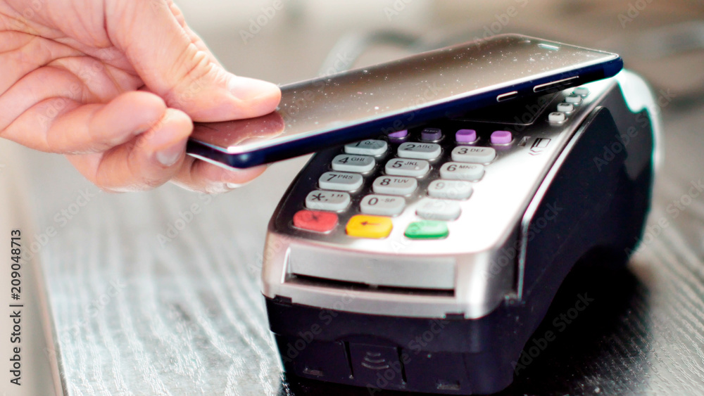 Fototapeta Customer paying with NFC technology by mobile phone on POS terminal.