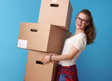 Happy Modern Woman Holding Stack Of Cardboard Boxes On Blue