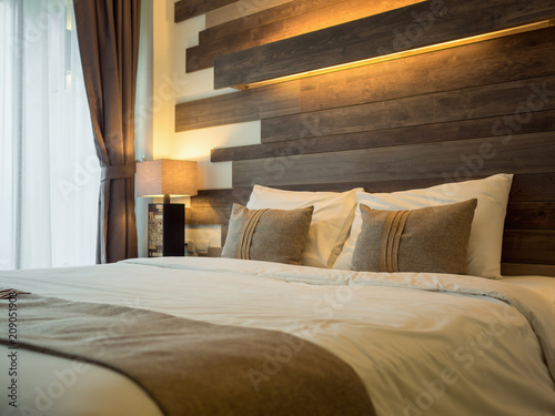 Photo  Empty double bed and lamp on side of bed in luxury and natural style bedroom is decorated with wooden boards