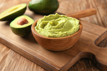 Bowl With Tasty Guacamole And Ripe Avocado On Wooden Board