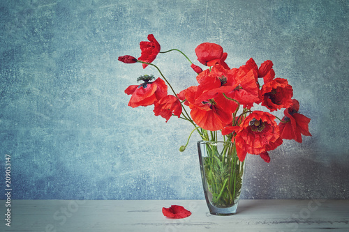 Red popies flowers in glass vase. Toned image. Copy space