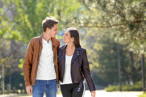Happy young couple walking together in city park Wallpaper Mural