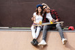 canvas print picture Young teen couple sitting on ramp and hangout at the skate park .Laughing and fun.