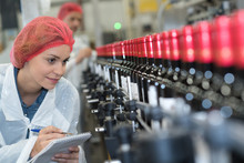 Woman Making Notes Beside Bottling Plant Production Line