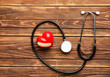 Medical stethoscope with heart on wooden background. Health care concept