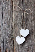 Two White Hearts Hanging On A Rope On An Old Weathered Wooden Surface