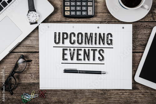 Text Upcoming Events written in notepad, Office desk with computer technology, high angle