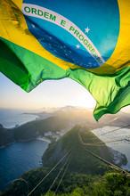 Brazilian Flag Shines Above The Golden Sunset City Skyline At Sugarloaf  Mountain In Rio De Janeiro Brazil.