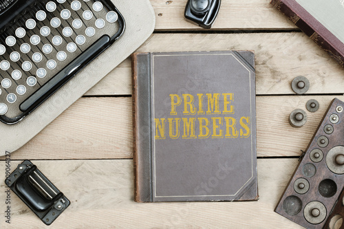 Fotografía  Text Prime Numbers on old book cover at office desk with vintage items