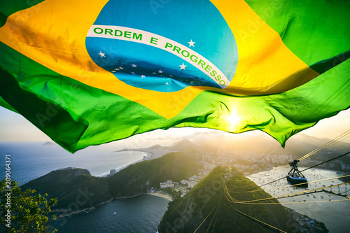 Brazilian flag shines above the golden sunset city skyline at Sugarloaf  Mountain in Rio de Janeiro Brazil Fotobehang