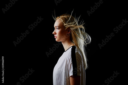 Fotografía  Portrait in profile of a beautiful blonde girl in a sports t-shirt on a black background