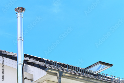 Stainless steel chimney and parts of a roof with an open roof window in front of a bright blue sky Fototapet