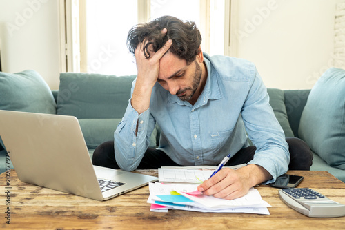 Fotografía  angry man paying bills as home with laptop and calculator