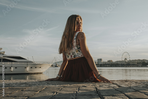Beautiful girl looking at camera while sitting at sea port shore at sunset, in Malaga, Spain.