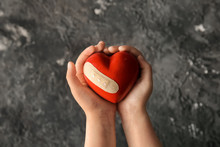 Hands Of Child Holding Red Heart With Plaster On Dark Textured Background. Health Care Concept