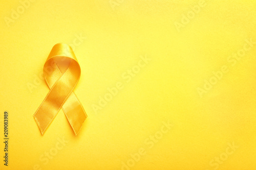 Fotografiet Yellow ribbon on color background. Cancer concept
