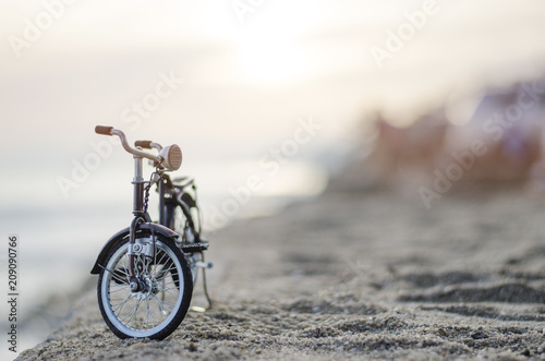 Foto op Canvas Fiets bicycle toy on beach sunset time holiday