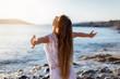 canvas print picture - Junge Frau streckt ihre Arme am Strand aus und genießt die Freiheit und Ruhe