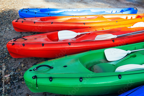 Closeup view of colorful canoe boats on the beach, ready for use Wallpaper Mural