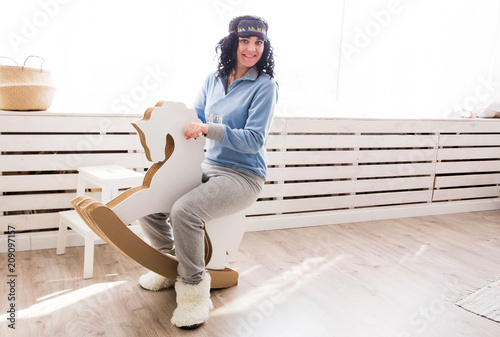 Fotografie, Obraz  young woman in pajamas sitting on a rocking horse