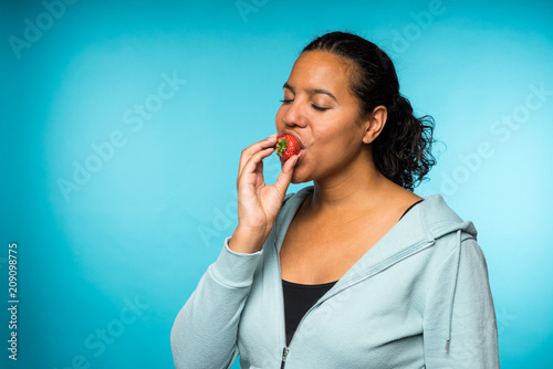Fotografia  Beautiful young mixed race woman in casual clothing eating and enjoying a fresh