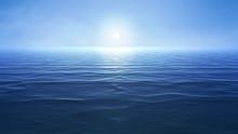 A Blue Ocean With Sun Over The Horizon