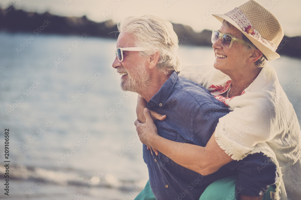 Fototapeta happy senior couple have fun and enjoy outdoor leisure activity at the beach. the man carry the woman on his back to enjoy together a retired lifestyle at the beach - obraz na płótnie