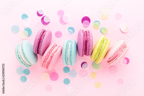 The row of colorful sweet macarons on pink background decorated with confetti Poster Mural XXL