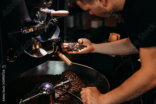 Man working at coffee production. Barista controling coffee grounds roasting process. - 209107126