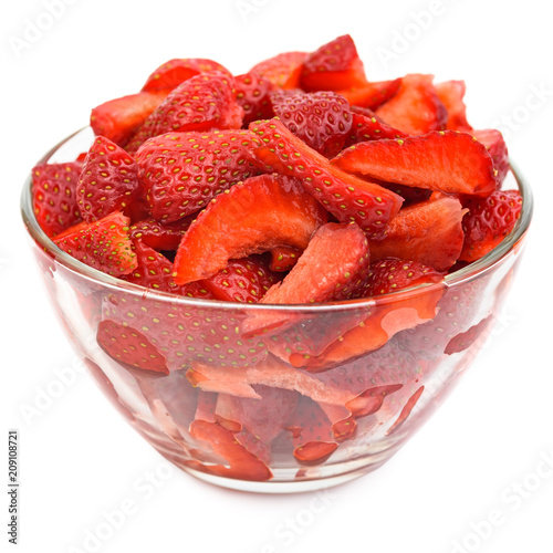 Chopped strawberries in transparent glas bowl isolated