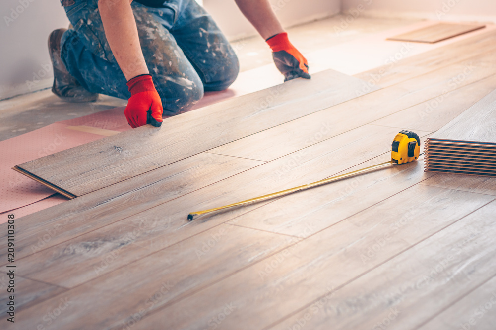 Fototapeta Working with hands installs a laminate board, professional flooring installation