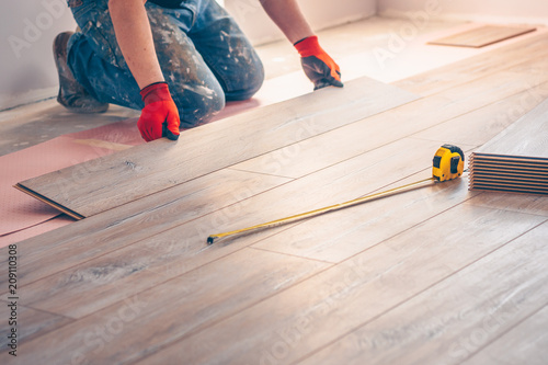 Working with hands installs a laminate board, professional flooring installation Canvas Print
