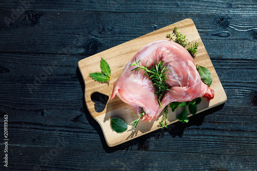 Fototapeta Preparation of rabbit meat for smoking. Raw rabbit legs, lime, onions, garlic, thyme and rosemary in rustic style, Sea salt, red, white pepper and coriander in clay pots on an old black rustic table. obraz