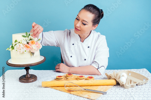 confectioner pastry chef baker woman decorates creamy white two-tiered wedding (birthday) cake with fresh flowers on table in studio on blue background Wallpaper Mural