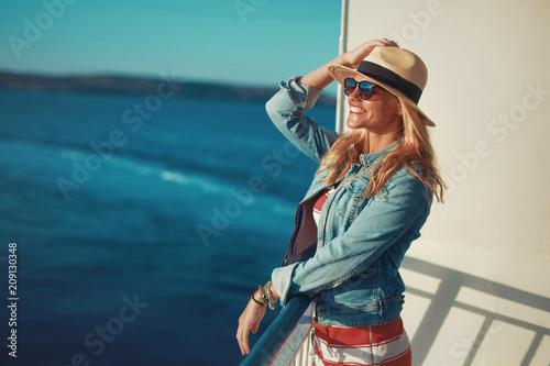 Young blonde woman traveler posing on cruise ship deck