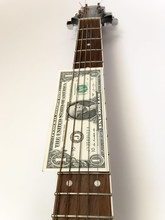 One Dollar On Guitar Fret Against White Background