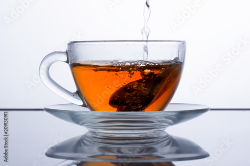 Foto op Plexiglas Thee in a transparent cup of tea is poured, black tea is poured