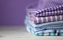 Many Kinds Of Cotton Fabrics In Stripes And Cage On A Lilac Background. Purple, Blue And Turquoise Fabrics For Sewing