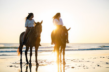 Teens Riding Horses At The Beach