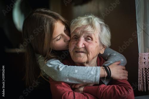 Obraz na plátne A little girl hugs her grandmother.