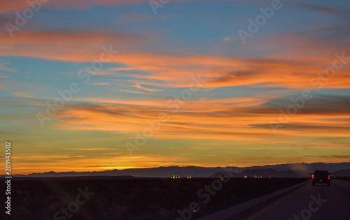 Fotografija Road going right towards sunset. Wispy, glowing clouds