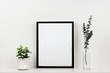 canvas print picture - Mock up black frame with plant and branches on a shelf or desk. White shelf and wall. Portrait frame orientation.