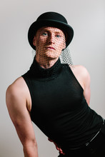 Elegant Man Wearing Bowler Hat With Veil And Rollneck Top, Cabaret Style Studio Shoot.