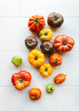 Fresh And Colourful Heirloom Tomatoes On White Tiles