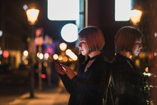 Blond Woman With Short Hair Using Her Smartphone On The Street In The Evening City.