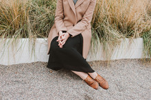 Anonymous Woman Sitting Among Dry Yellow Grass