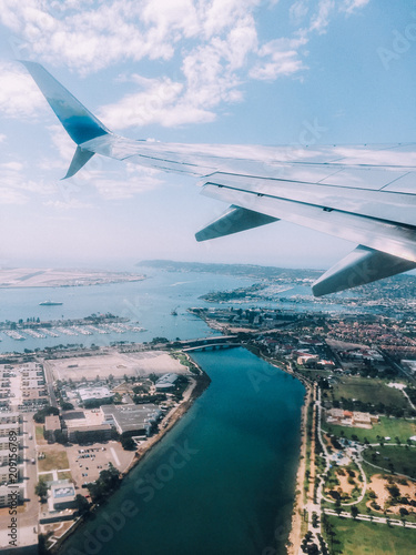 Airplane departing into a beautiful sky with amazing landscape water view below.