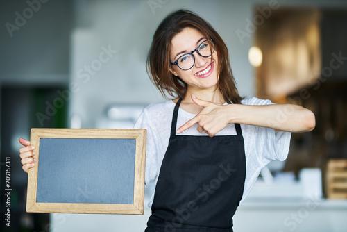 happy waitress holding blank chalkboard sign