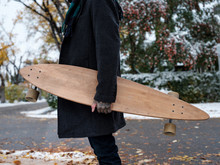 Man Holds A Longboard With His...